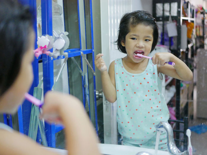 Little Asian baby, 38 months old, girl was brushing teeth in front of a mirror by herself - child development by allowing them to do things by themselves Baby Girl Asian  Kid Young Toddler  Brushing Brushed Brushes Teeth Tooth By Oneself By Herself Learning Learned At Home In Front Of Mirror Toothbrush Lifestyles Childhood People Selective Focus Little Her Own Standing Holding Development