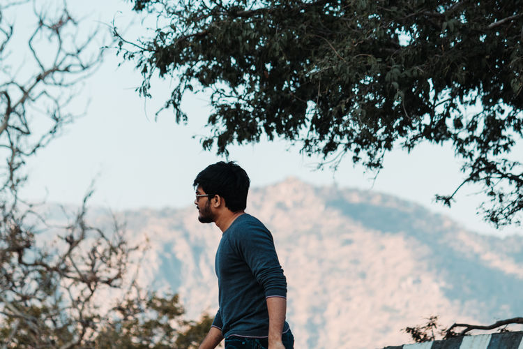 Young man standing on road against trees and mountain