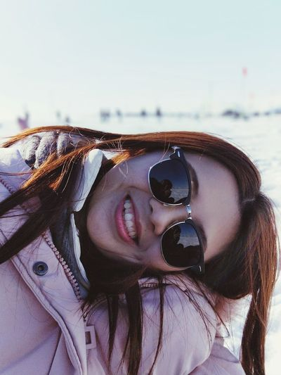 Portrait Of Woman Smiling While Wearing Sunglasses Against Sky