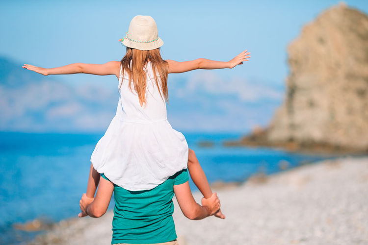 Rear view of father with daughter on shoulder at beach