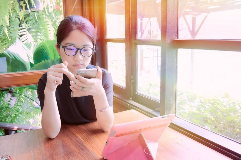 EyeEm Selects Asian girl using smartphone and tablet to do business. Window Indoors  Eyeglasses  Table Sitting Wireless Technology Lifestyles Girl Portrait Happiness Pretty Fashion Asian  Casual Clothing Young Women Leisure Activity Daylight Business Smart Phone Tablet Computer Modern