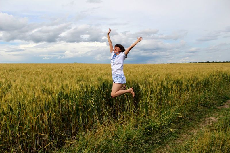 Cheerful young woman with arms raised jumping on field against cloudy sky