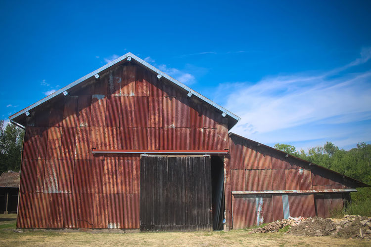 Old barn on field against blue sky