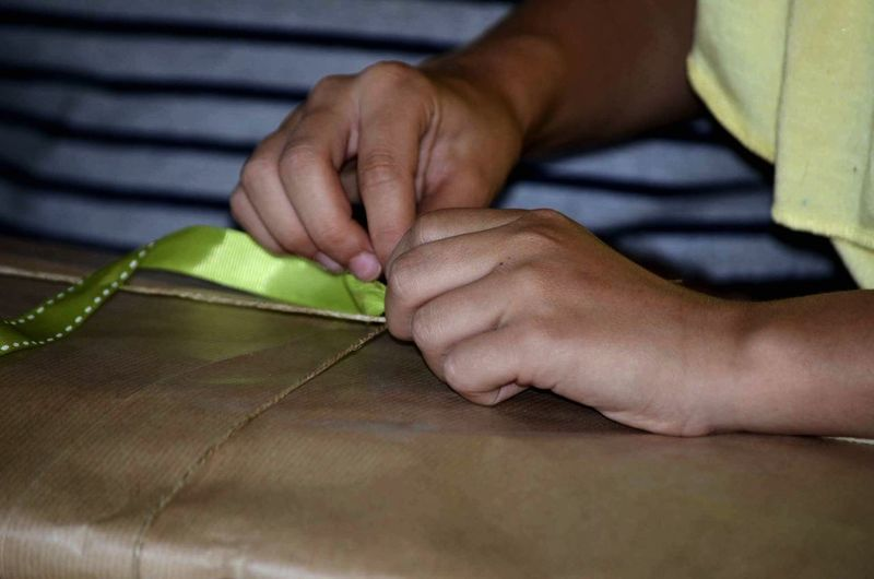 Cropped image of girl unwrapping present at home