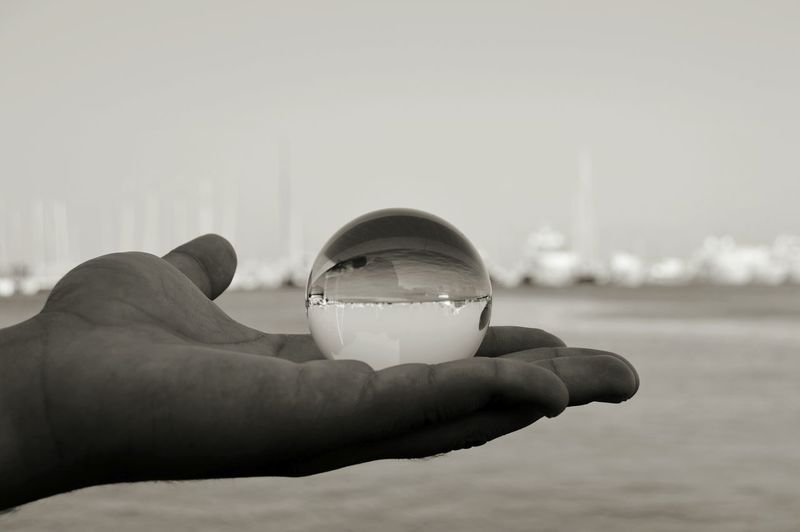 Close-up of hand holding crystal ball by sea against sky