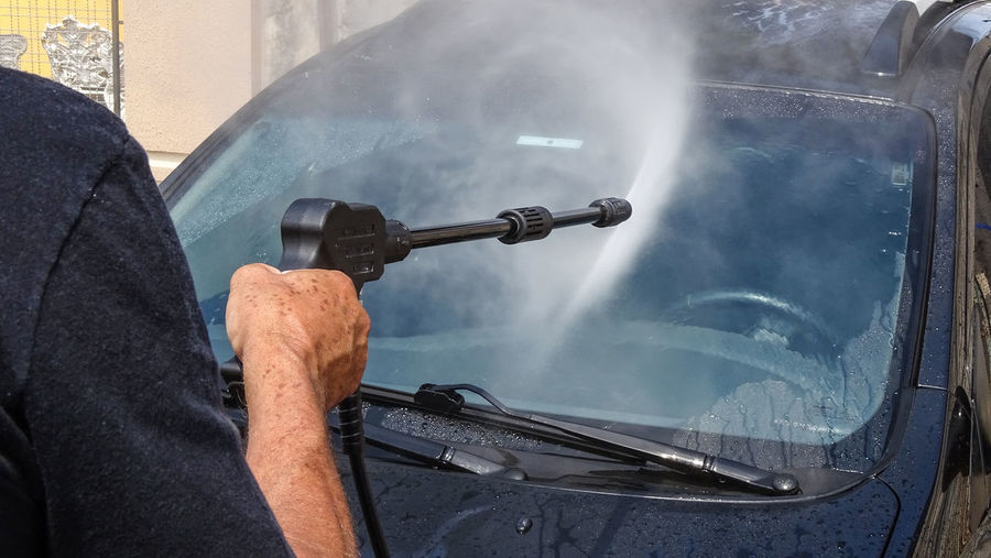 Man spraying water on car windshield