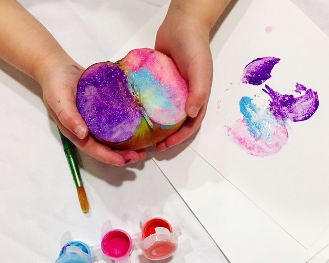 Close-up of hand holding painted apple