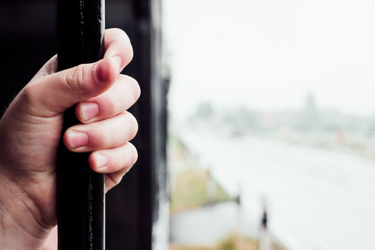 Hold Tight Black Color Body Part Close-up Day Finger Focus On Foreground Hand Holding Holding On Human Body Part Human Finger Human Hand Lifestyles Men Metal One Person Outdoors Real People Train Unrecognizable Person Window