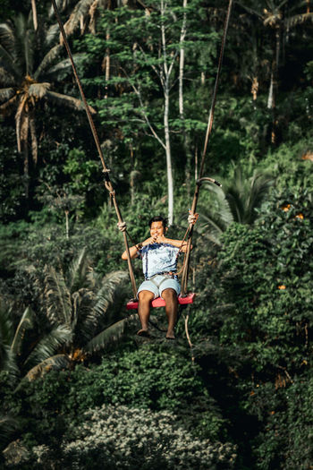 Man sitting on swing in forest
