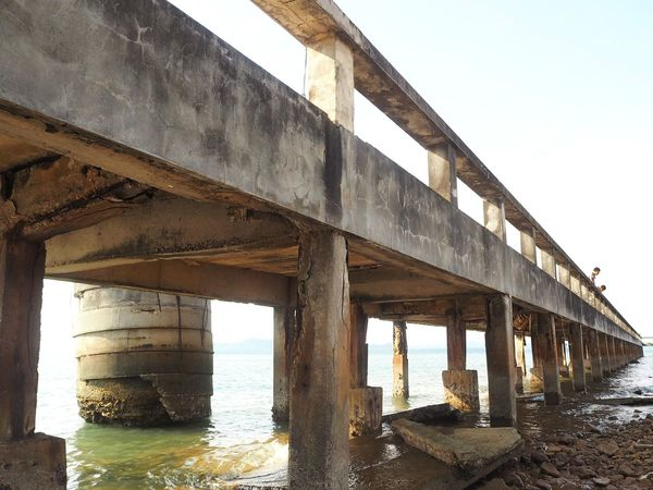 Under the pier. HelloEyeEm Thailand Awesome Old Ruin Rocky Coastline Bridge Bridge - Man Made Structure Connection Built Structure Water Architecture Transportation Sky Nature Clear Sky Sea Day No People Architectural Column Low Angle View Beach Land Underneath Concrete Overpass