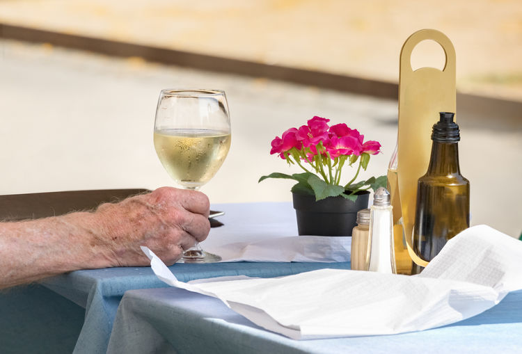 Alcohol Background Bar Caucasian Drink Enjoyment Glass Hand Holding Leisure Lunch Male Man Maturity Old Outdoor People person Restaurant Retirement Senior Street Table Vine White Wine Wineglass