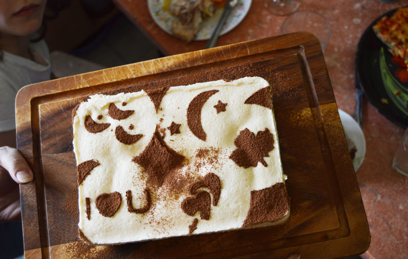 Tiramisu decorated with drawings stencil of cocoa on dark wooden board