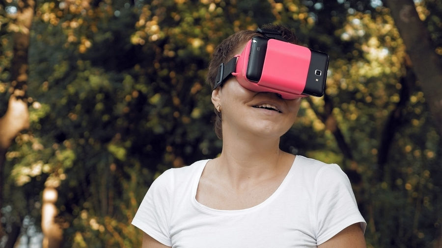 Woman using virtual reality simulator against trees