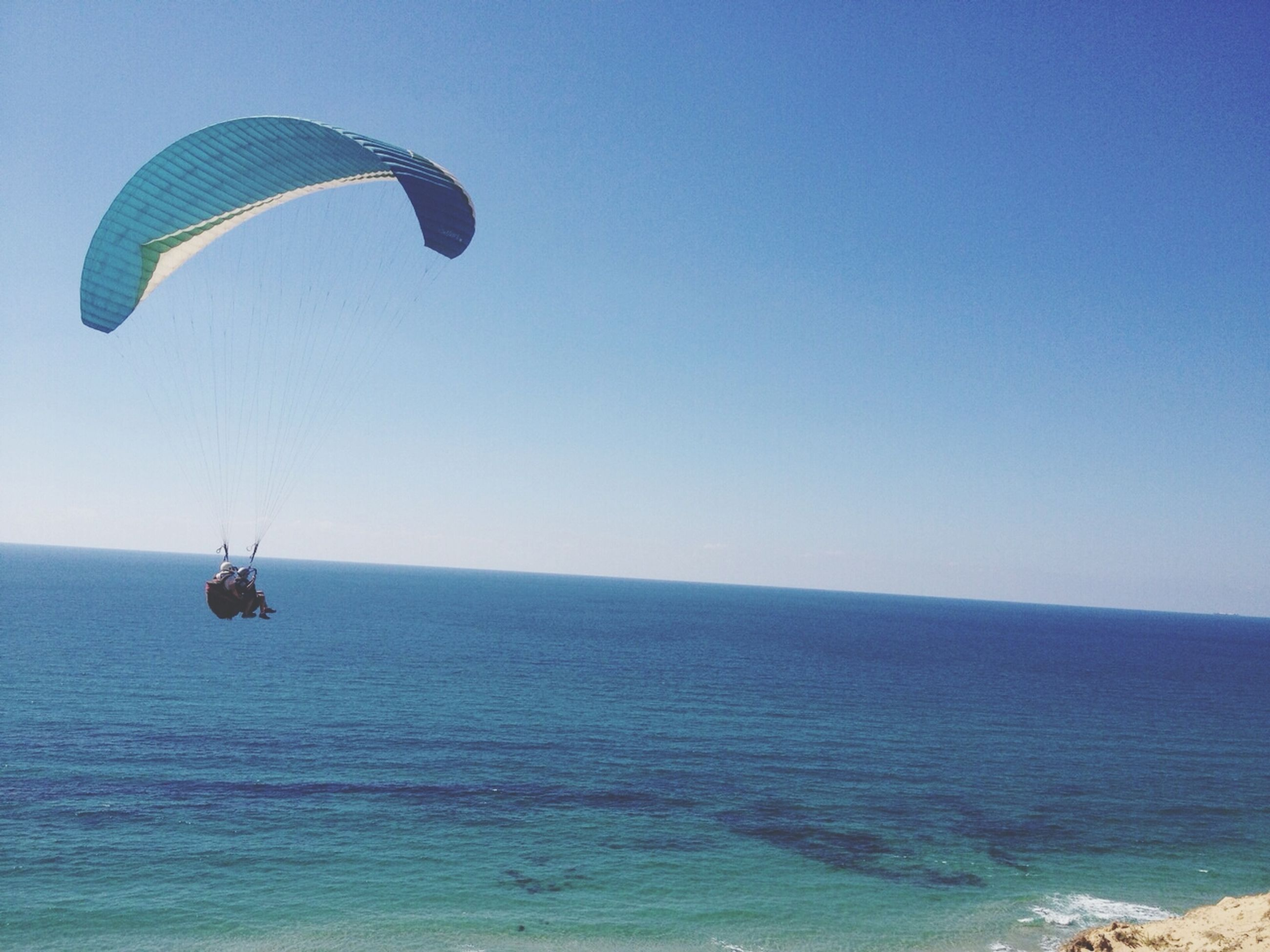 sea, water, clear sky, horizon over water, beach, parachute, blue, tranquility, tranquil scene, copy space, scenics, extreme sports, mid-air, adventure, vacations, flying, sport, leisure activity, beauty in nature, nature