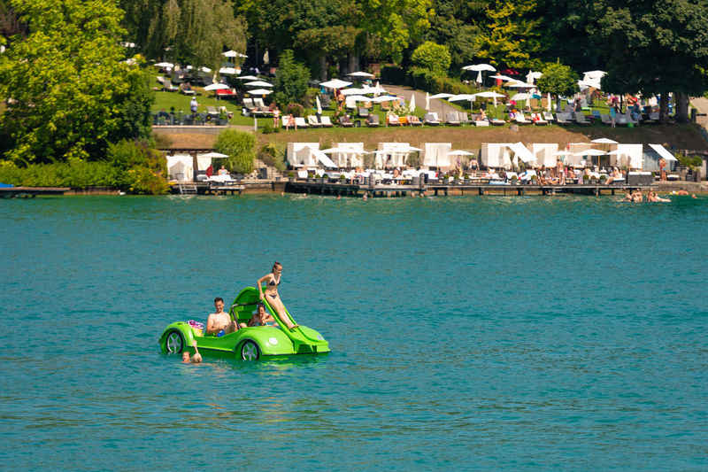 WORTHERSEE, AUSTRIA - AUGUST 08, 2018: View from the boat to the lake and coastline. Local residents and tourists swim, driven by motorboats and use other forms of water recreation. Nature Day Outdoors Austria Carinthia Carinthian Lakes Tourist Tourists Lake Wörthersee Recreation  Leisure Landscape Water Sea Boats Motorboat Speedboats Summer People Holidays Fun Travel Beach Resort Lifestyle Sunny Rest Joy Waves Europe Alps Alpine Alpine Lake Nautical Vessel Transportation Tree Leisure Activity Plant Group Of People Men Trip Vacations Architecture Holiday Adult Lifestyles Enjoyment Inflatable