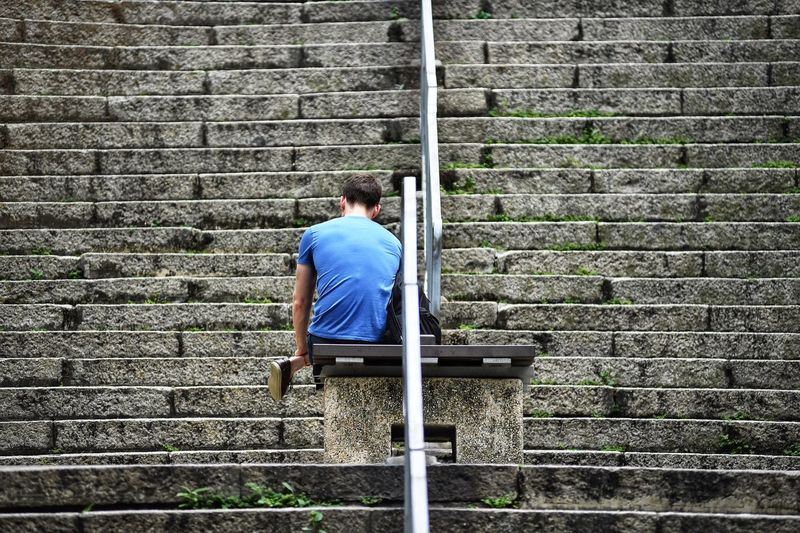 Rear View Of Man Sitting On Bench On Steps