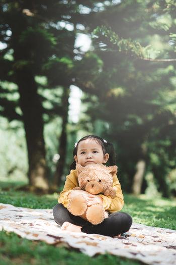Portrait of cute boy sitting on toy against trees