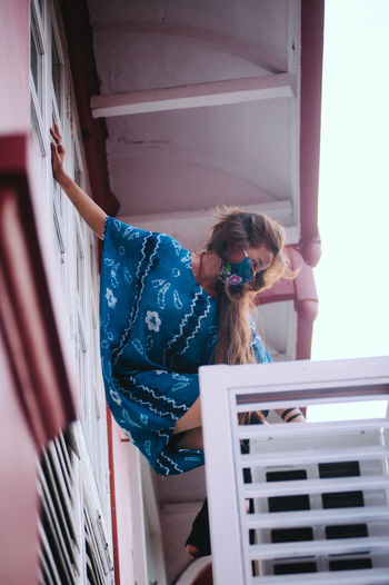 Low angle view of woman standing on balcony