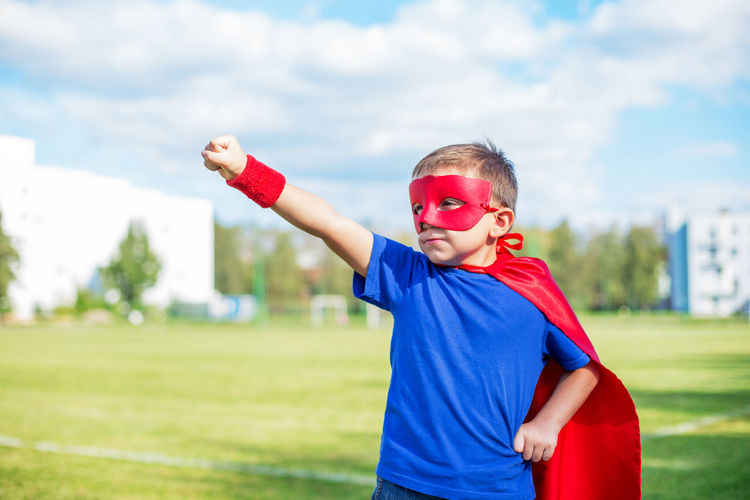 Boy in superman costume standing on road against sky
