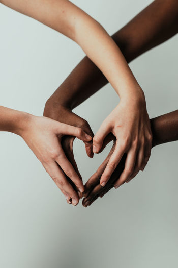 Cropped hands of women making heart shape against gray background