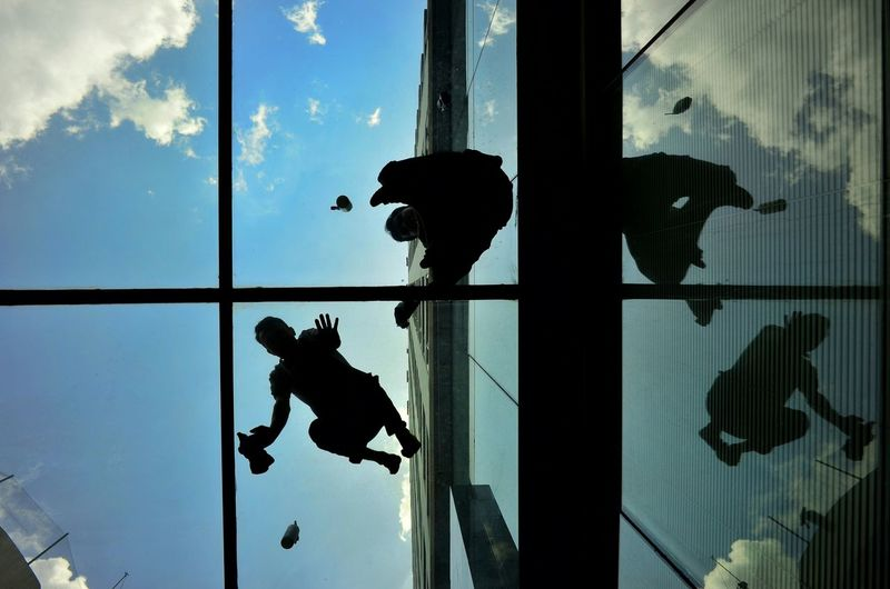 Directly below shot of window washers cleaning skylight