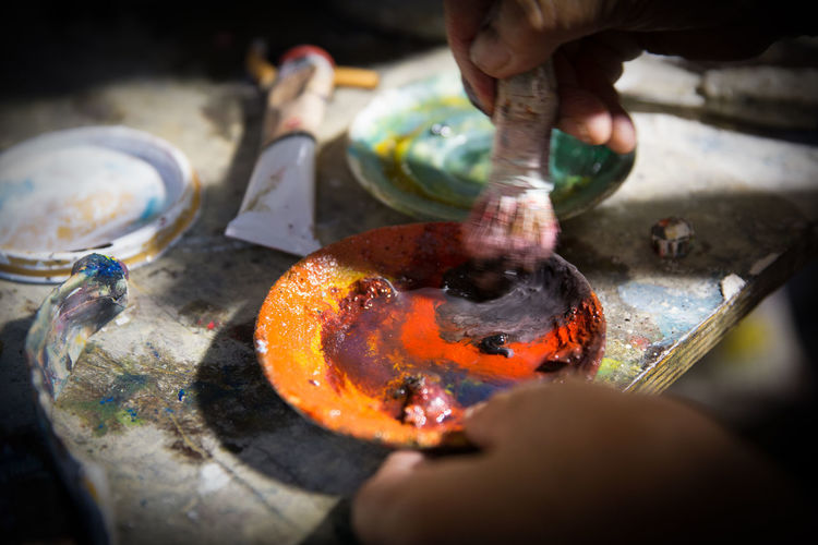 Cropped hands of artist mixing paint in plate