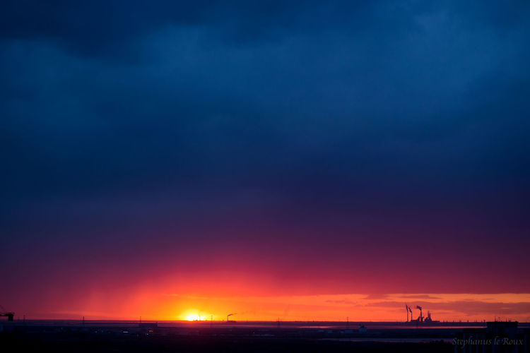 Dramatic sunset with a power station releasing smoke into the air Blue Cloud - Sky Clouds And Sky Dramatic Sky Factories Industry Landscape Multi Colored Night No People Scenics Sea Silhouette Sky Smoke Sunset First Eyeem Photo