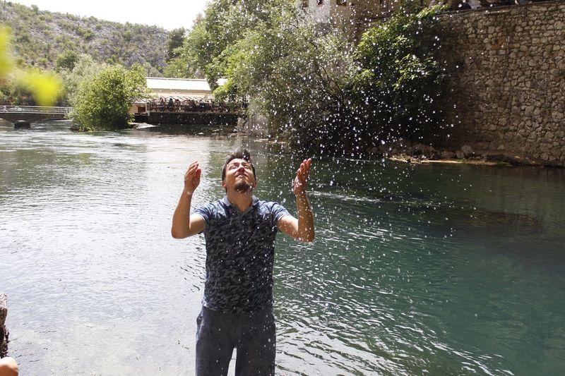 Smiling man splashing water at riverbank