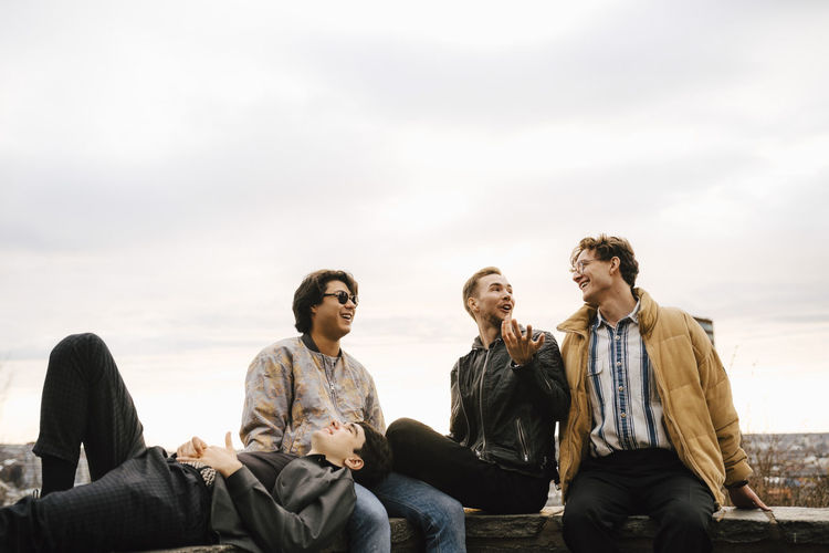Young men sitting against sky