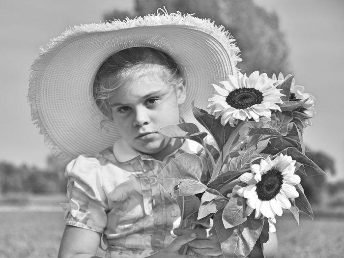 Portrait of little girl holding sunflowers on field