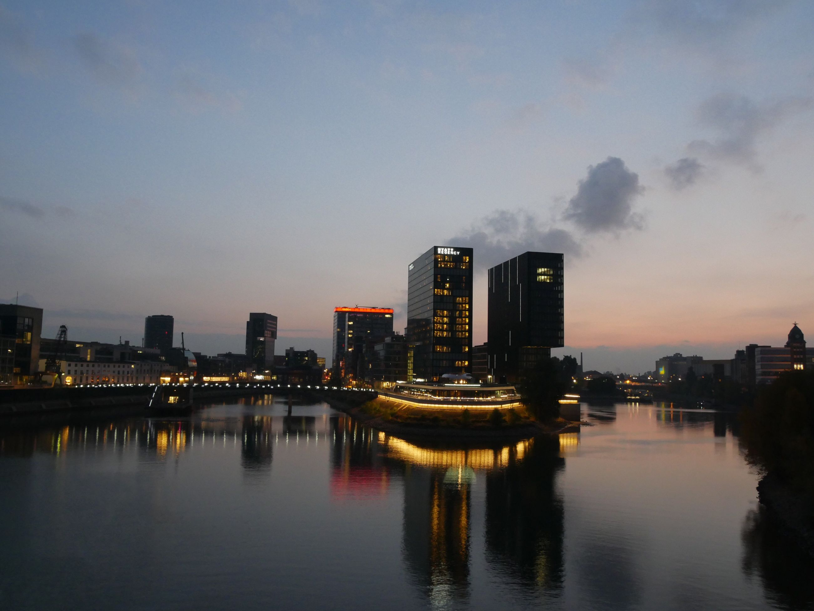 architecture, building exterior, built structure, illuminated, water, reflection, waterfront, city, river, sky, skyscraper, cloud, building story, tall, calm, modern, multi colored, ocean, financial district, sea, water surface, urban skyline, no people, development