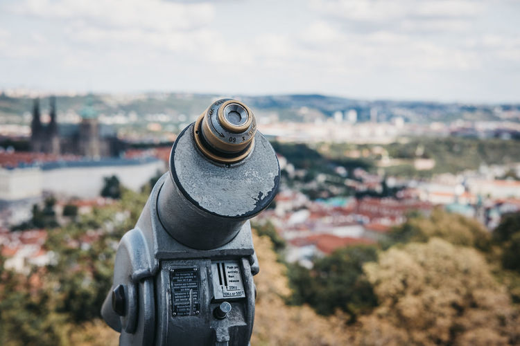 Coin operated binoculars on the viewing platform in prague, in summer, the blurred city background.