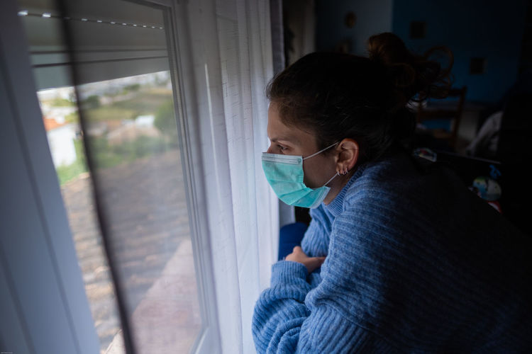 Close-up of woman wearing mask looking through window at home