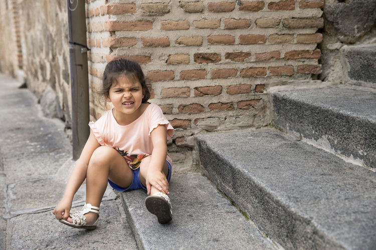 Girl Making Face While Sitting On Footpath Against Brick Wall