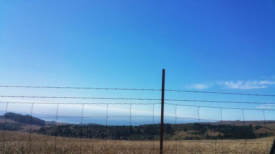 Foggy ocean view from country mountain road. Disruption - Barbed wire fence. Barbed Wire Disruption Squares Zen Background Copy Space Golden Headland Distance Ocean Field Dreams Countryside Rural Road Day Trip Roadside View Metal Post Fence Post Lines vanishing point Pattern Foggy White Water Clear Sky Rural Scene Mountain Sky Landscape
