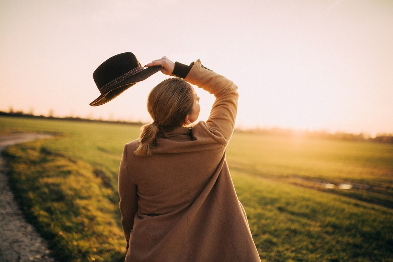 Rear View Of Woman Holding Hat On Grassy Field Against Sky