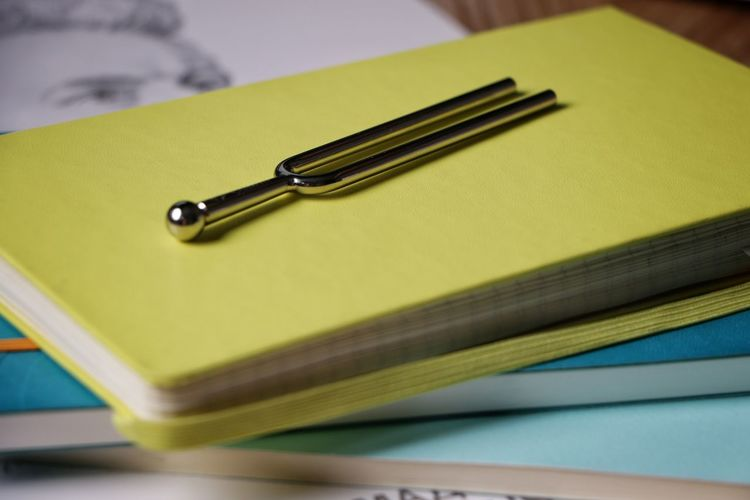 Close-up of tuning fork on notebook