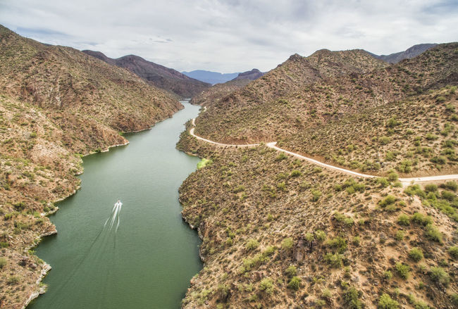 Overview of Salt River at Apache trail scenic drive, Arizona Arizona Beauty In Nature Boat Calm Cloud Day Elevated View High Angle View Idyllic Mountain Nature No People Outdoors Remote River Rocky Salt River Canyon Scenics Sky Stream Tontonationalforrest Tranquil Scene Tranquility Water