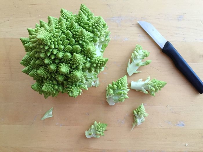 Directly above shot of romanesque cauliflowers and knife on cutting board