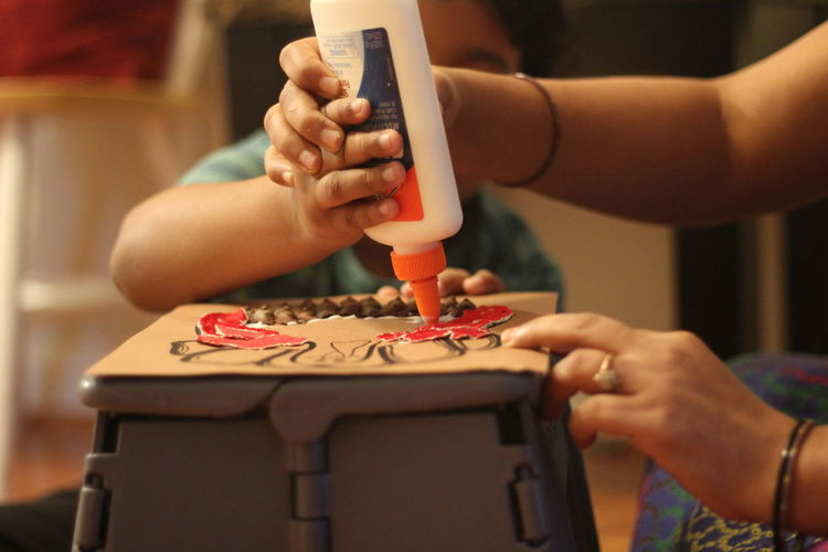 Cropped Hands Of Mother And Son Making Craft On Table