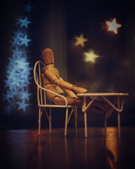 Wooden Doll On Small Chair At Table Against Christmas Lights