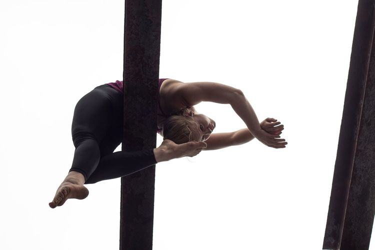 Low Angle View Of Gymnast Performing On Balance Beam Against Clear Sky