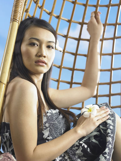 asian woman sitting on the rattan swing Asian  Confidence  Happiness Happy One Person Only Woman Attractive Beautiful Woman Beauty In Nature Close-up Day Head And Shoulders Lifestyles Mixed Race Person One Person Portrait Real People Simplicity Sky Women Young Adult Young Women