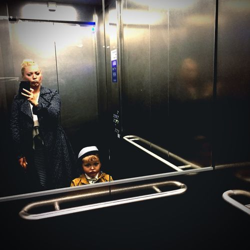 Self portrait of woman and child in elevator