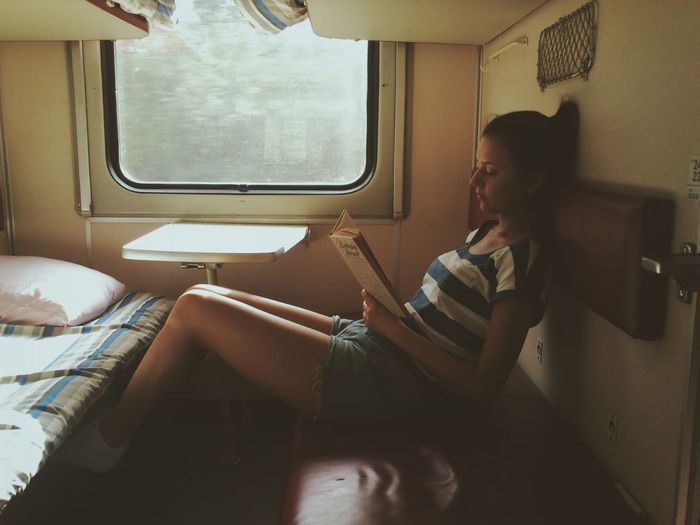 Young woman reading book while resting in train