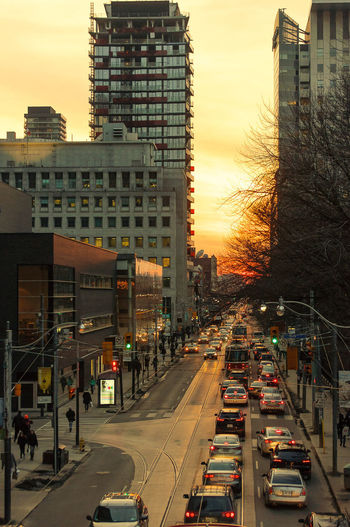 Vehicles on road against buildings at sunset