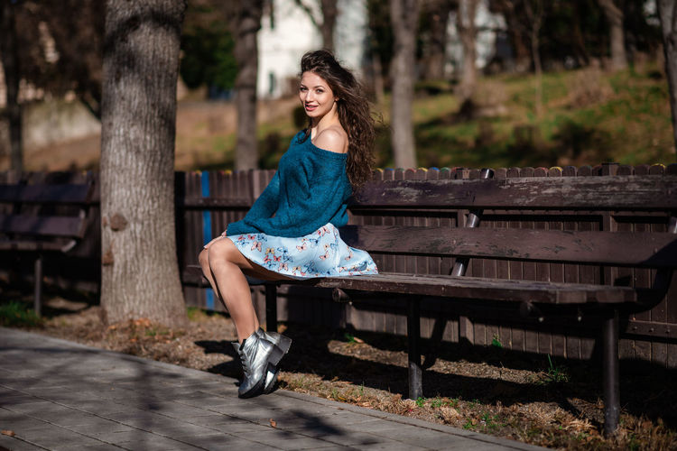 Portrait of woman sitting on bench in park