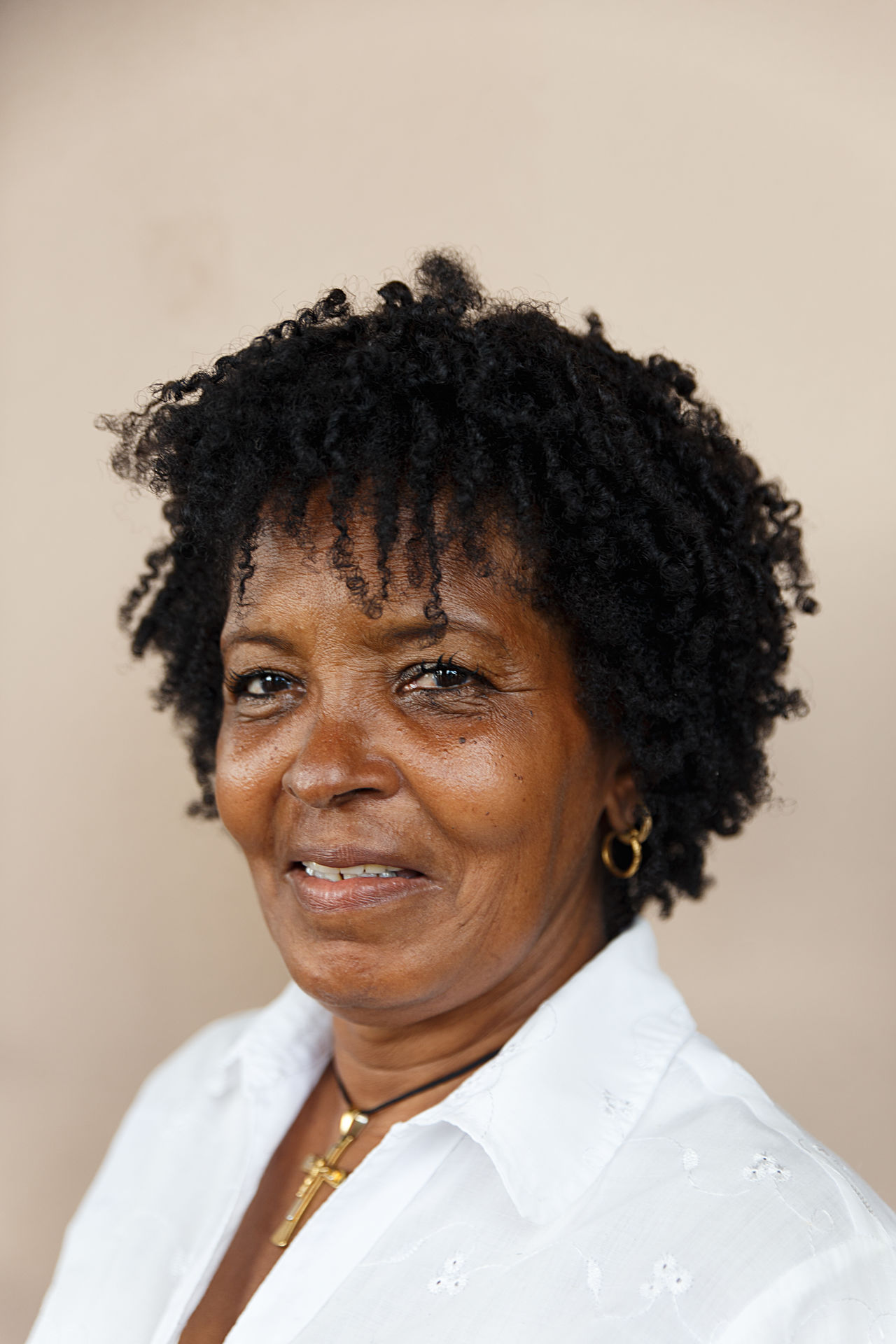Close-up portrait of smiling mature woman against wall