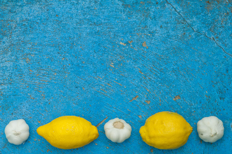 High angle view of garlic and lemons on blue wooden table