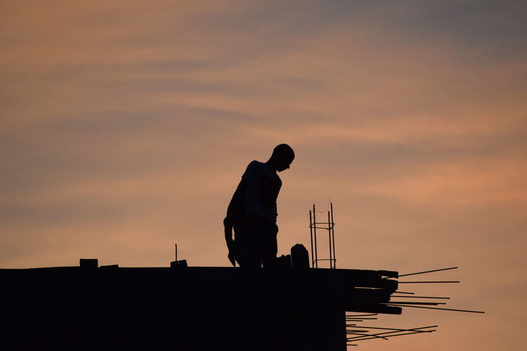 Silhouette worker standing on building against cloudy sky during sunset